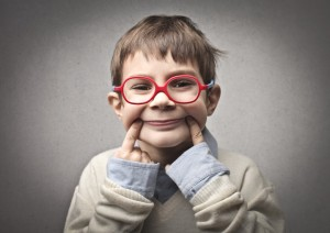 child in red glasses smiling